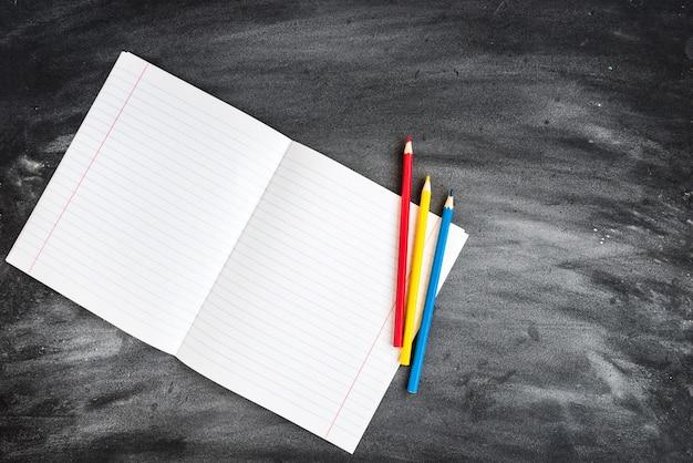 Цветные карандаши, тетрадь на фоне черной доски. снова в школу концепции.