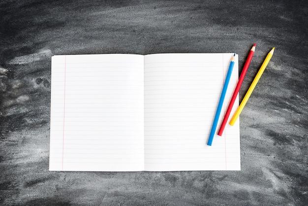 色鉛筆、ブラックボードの背景のお手本。学校のコンセプトに戻る。