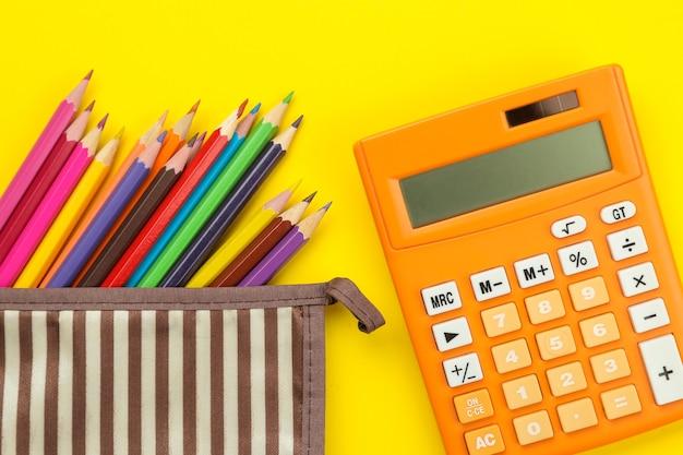 学校の筆箱に色鉛筆と明るい紙の黄色の背景に電卓。オフィスツール。教育。上面図。