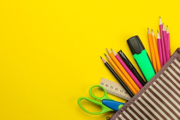 밝은 종이 노란색 배경에 학교 연필 케이스에 색연필. 사무실 도구. 교육. 평면도.