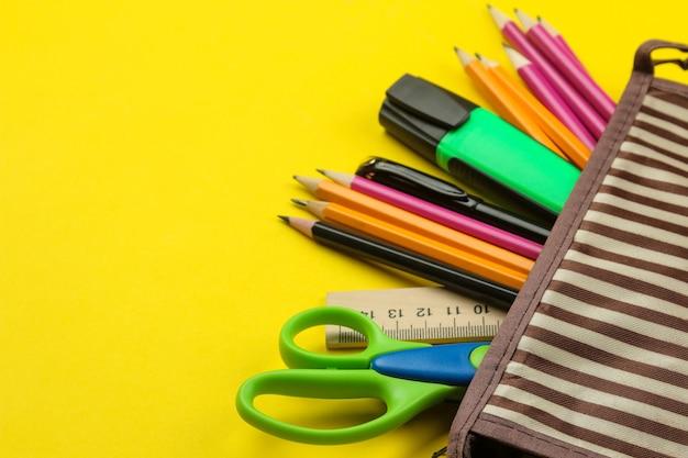밝은 종이 노란색 배경에 학교 연필 케이스에 색연필. 사무실 도구. 교육.