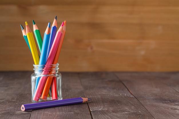 Цветные карандаши в стеклянной банке на деревянной поверхности