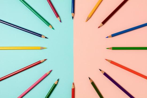 青とピンクの背景に分離された色鉛筆