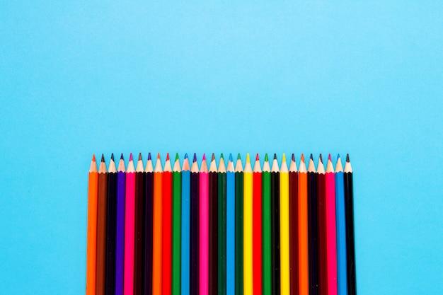 青色の背景に色鉛筆が並んでいます。フラット横たわっていた、トップビュー