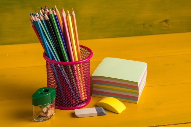 Color pencils in metal grid container on the yellow board
