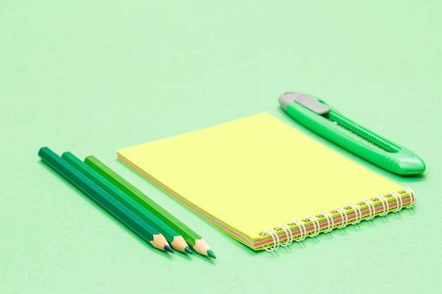 Цветные карандаши, блокнот и нож для бумаги на зеленом фоне. снова в школу концепции. школьные принадлежности. малая глубина резкости.