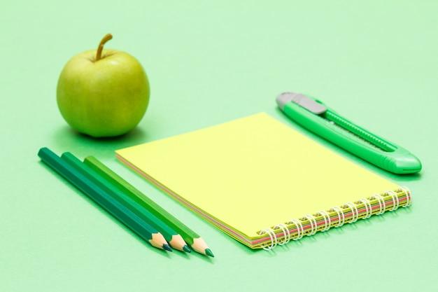 Цветные карандаши, блокнот, нож для бумаги и яблоко на зеленом фоне. снова в школу концепции. школьные принадлежности. малая глубина резкости.