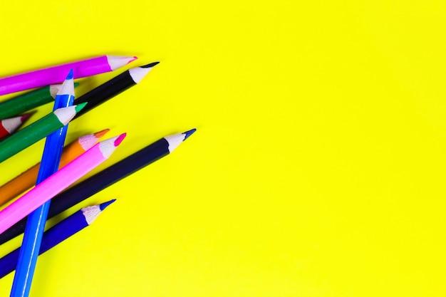 Цветные карандаши на желтом фоне, фон для дизайнеров, место для текста