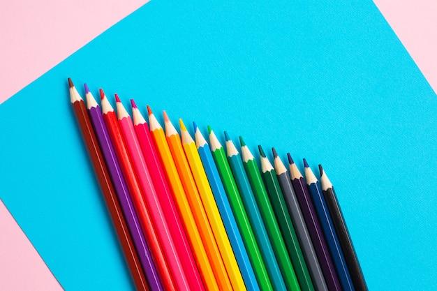 Цветные карандаши на синем и розовом фоне.