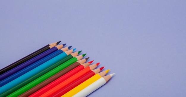 Цветные карандаши на фиолетовом фоне для проектов и объявлений