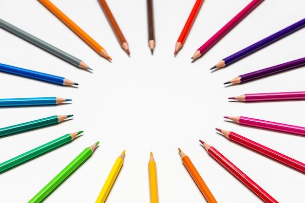 白い背景の上の色鉛筆。クローズアップ。学校のコンセプトに戻る。