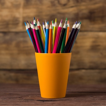 Color pencils in orange grocery on wooden
