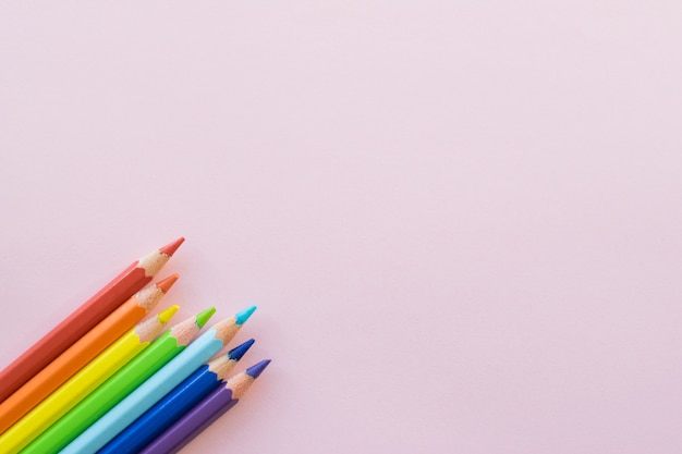 Color pencils on pink background, copy space. office supplies, back to school.