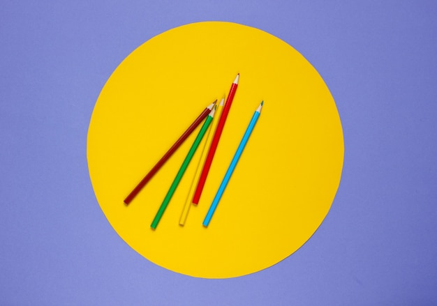 Color pencils on a purple with a yellow circle