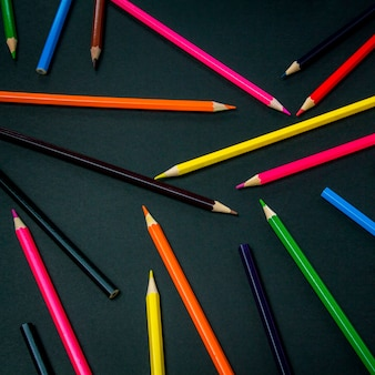 Color pencils scattered throughout the frame on a black background. flat lay, top view