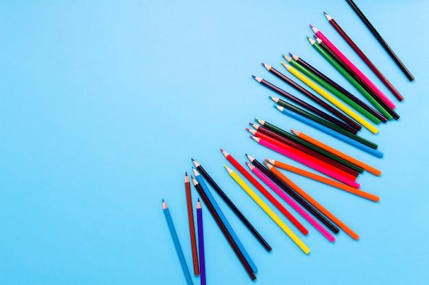 Цветные карандаши разбросаны на синем фоне. плоская планировка, вид сверху