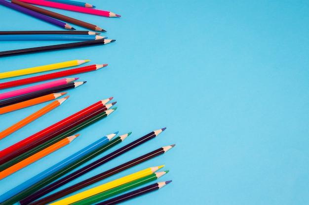 青色の背景に散らばって色鉛筆