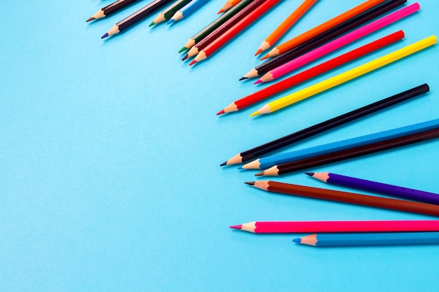 青色の背景に散在している色鉛筆