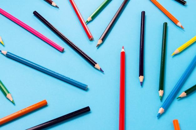 Цветные карандаши разбросаны по всей рамке на синем фоне. плоская планировка, вид сверху