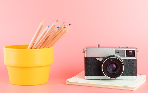 Color pencils with photo camera for art concept on pink