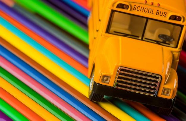 Color pencils on yellow school bus school supplies