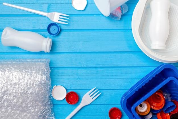 Цветные пластиковые отходы для переработки на синем фоне