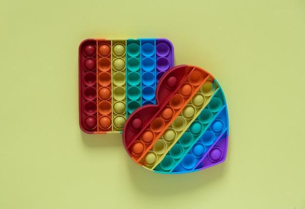 子供のためのカラーポップそれの抗ストレスおもちゃ。黄色の背景に分離された虹のハート型。 2つのおもちゃ-正方形でハートの形をしています。おもちゃをポップします。