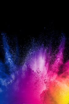 Color powder explosion cloud on black background. Freeze motion of color dust  particles splashing.