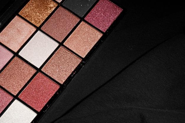 Цветная профессиональная косметическая палитра на темном фоне, крупный план