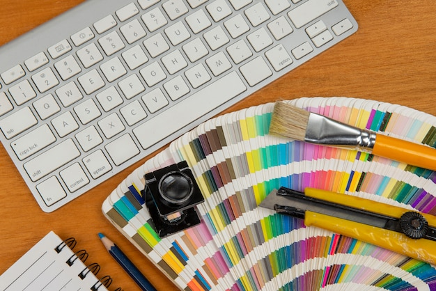 Color scale with stylus and magnifying glass on it and a notebook