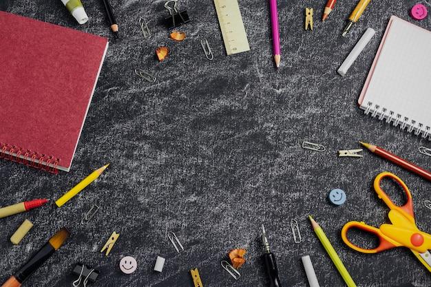 Color school supplies on blackboard