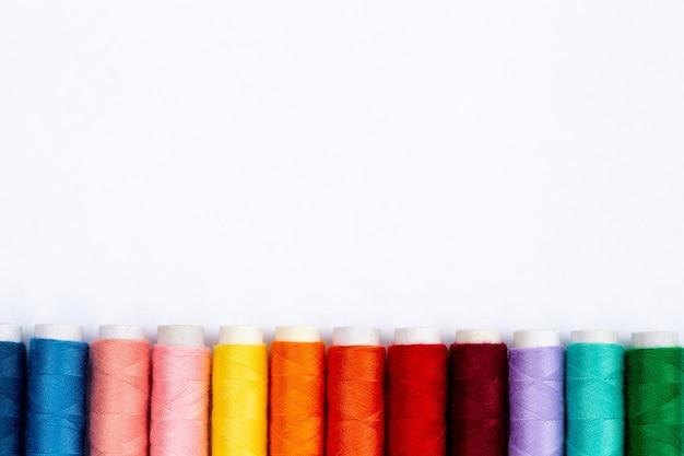 흰색 배경, 복사 공간 평면도에 컬러 바느질 스레드. 프리미엄 사진