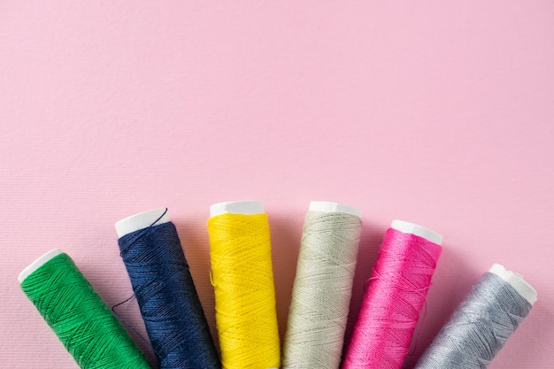 Color sewing threads on pink background