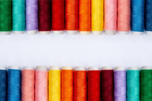 Color sewing threads on white background, top view.