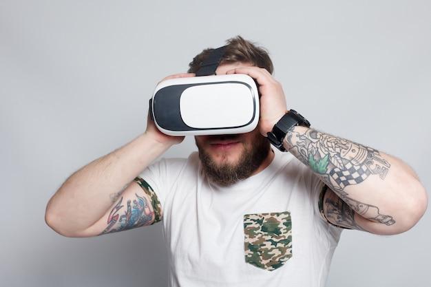 Цветной снимок молодого человека, просматривающего виртуальную реальность, устройства, с помощью которого можно испытать виртуальную реальность на мобильном телефоне. человек касается руки. размытые фотографии