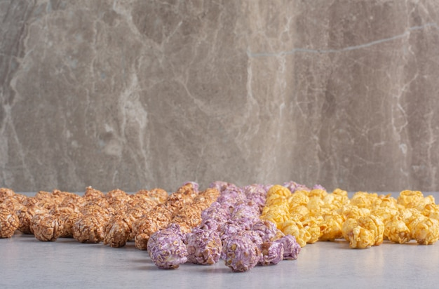 Caramelle popcorn ordinate per colore allineate sul marmo.