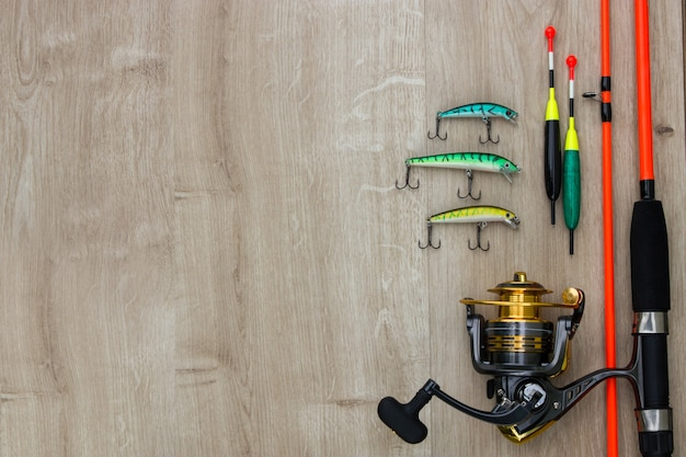 Color spinner lures fishing bytes floats spinning reel and orange rod on wood place for text