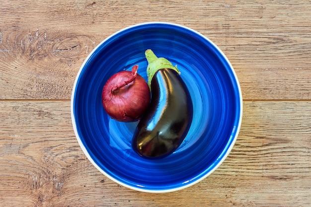 파란색 접시에 붉은 달콤한 양파와 보라색 가지의 색 정물 보라색 전구