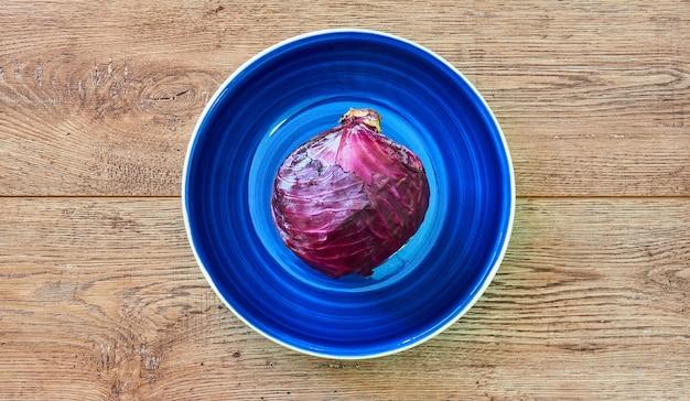 색상 정물 - 나무 탁상에 있는 깊고 푸른 접시에 붉은 양배추의 보라색 머리