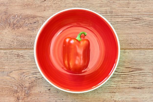 색상 정물 - 나무 탁상에 있는 빨간 접시에 달콤한 피망의 빨간 꼬투리