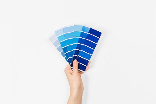 手に2020年の色を持つ色見本-クラシックブルー。カラートレンドパレット。