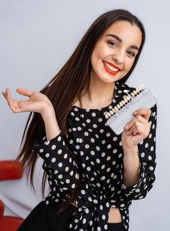 Цветная палитра зубов для отбеливания в стоматологической клинике. девушка на размытом фоне. закройте вверх.