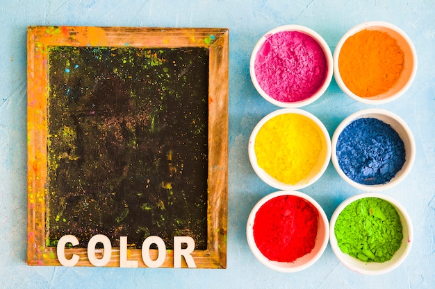 Color text on wooden slate with holi color powder in the white bowls
