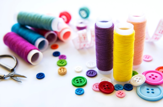 Color threads and sewing accessories on white surface