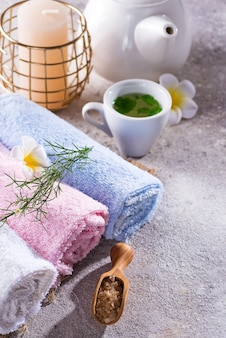 Color towels with flower, spoon of salt, on bamboo mat, bath spa treatment and green tea on stone table, copyspace