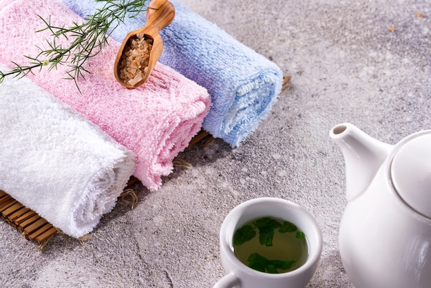 Color towels with flower, spoon of salt, on bamboo mat, bath spa treatment and green tea on stone table