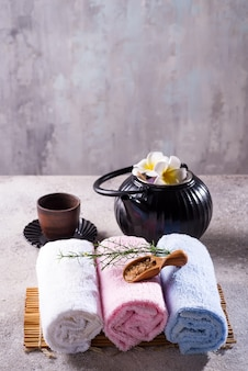 Color towels with green leaves, spoon of salt and detox tea on bamboo mat and stone table