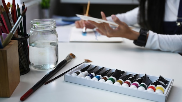 Color tube of water color or oil color and paintbrush on white table with female artist