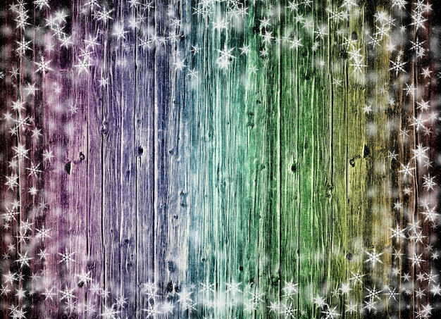 Color wood wall texture with white snow and stars. christmas background