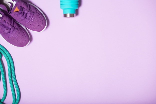 Colored accessories for rhythmic gymnastics, fitness, running. green jump rope, blue water bottle and lilac sneakers on a light background with copy space
